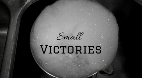 """Sink with big bowl full of soapy dishwater. In the middle it says """"Small Victories"""""""